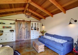 Sliding repurposed wood barn doors hide a fold out Murphy bed and turns the music room into a guest house.